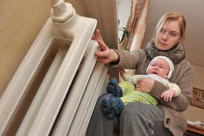 Женщина с ребенком греется у батареи в холодной квартире.